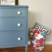 A smokey blue dresser with white knobs