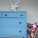 A sky blue dresser with some oversized knobs