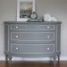A grey demi lune dresser with white accents
