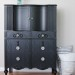 A tall black dresser with glass knobs