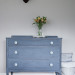 A grey-blue-purple dresser with soft blue knobs